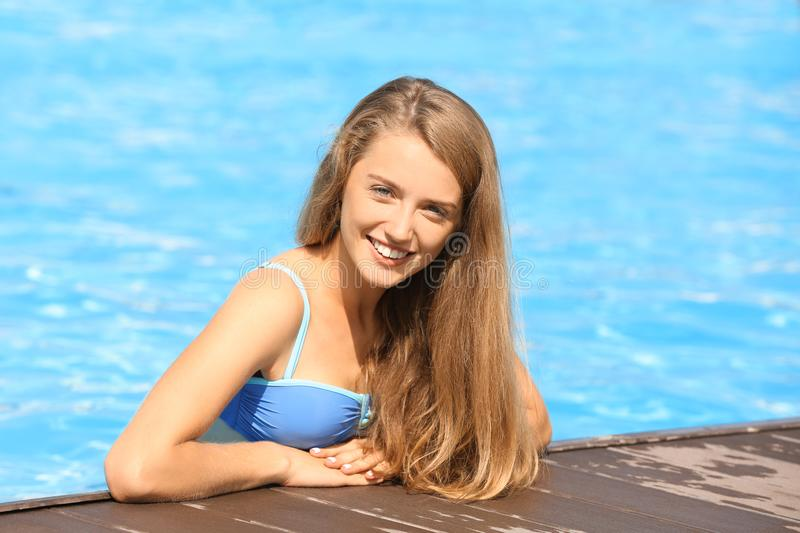 Beautiful young woman in swimming pool on sunny day stock images