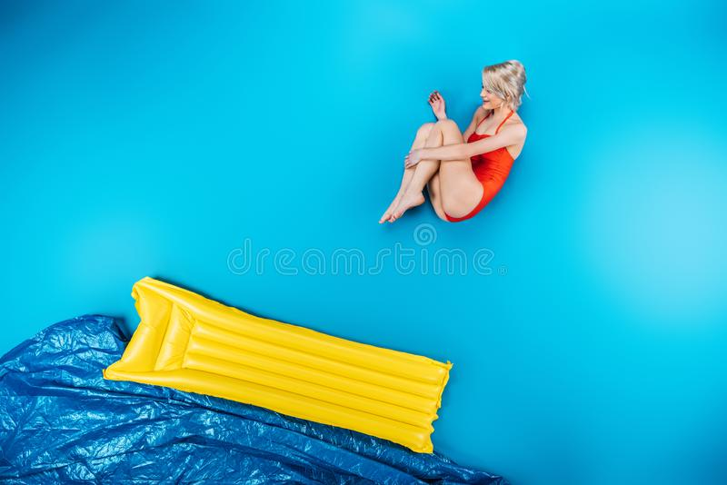 beautiful young woman in swimsuit jumping on inflatable mattress stock photography