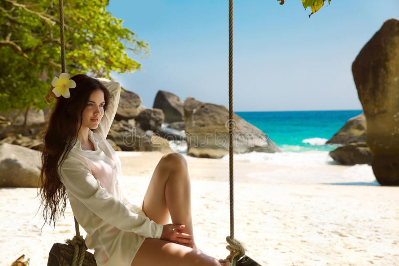 Beautiful young woman on a swing resting on exotic beach with white sand by sea blue water, seashore. Wellness. Rock. Lifestyle. royalty free stock photos