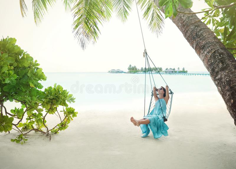 Beautiful young woman on swing at tropical stock photos