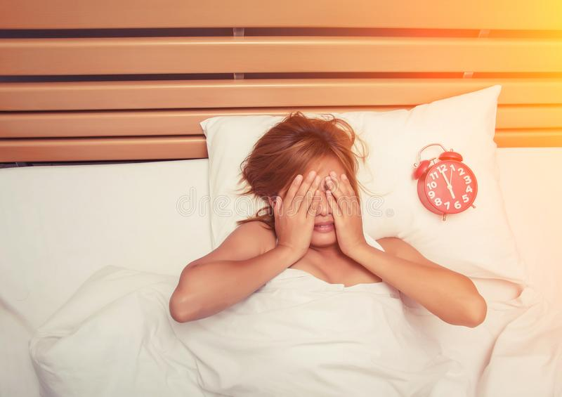 Beautiful young woman take hands off her face on the bed in the stock image