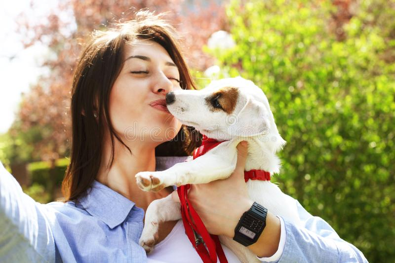 Beautiful young woman takes selfie of her kissing cute jack russell terrier puppy on picnic in park, green grass & foliage backgro stock photos