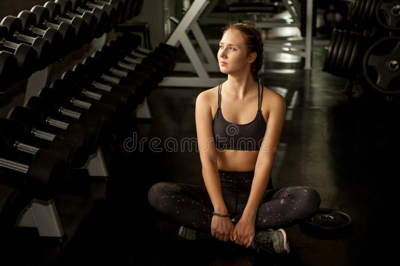 Beautiful young woman taking a break from exercise sitting cool down relaxation in fitness gym healthy .girl in sportswear workout. Rest near dumbbells shelf in royalty free stock photo