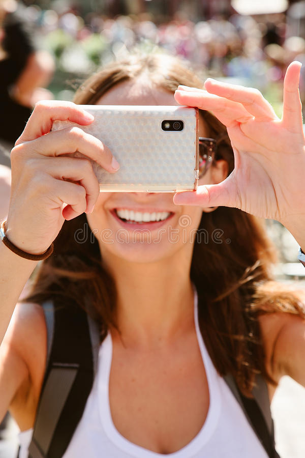 Beautiful young woman taking photos with mobile phone. Portrait of a woman taking photos with mobile phone royalty free stock photo