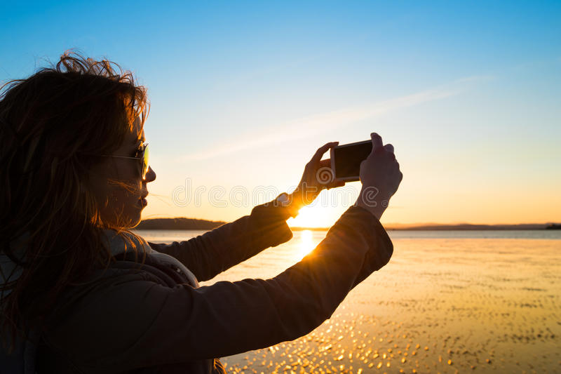 Beautiful young woman taking picture of herself, selfie, on a beach stock photos