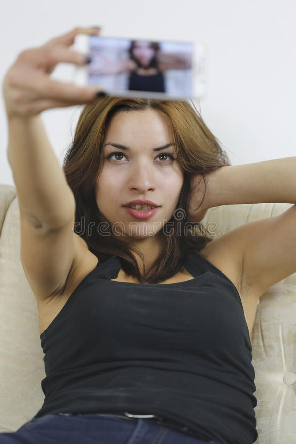 Beautiful young woman taking selfie. Girl photographing herself with cell phone. Beautiful young woman photographing herself with phone sitting in sofa stock photography