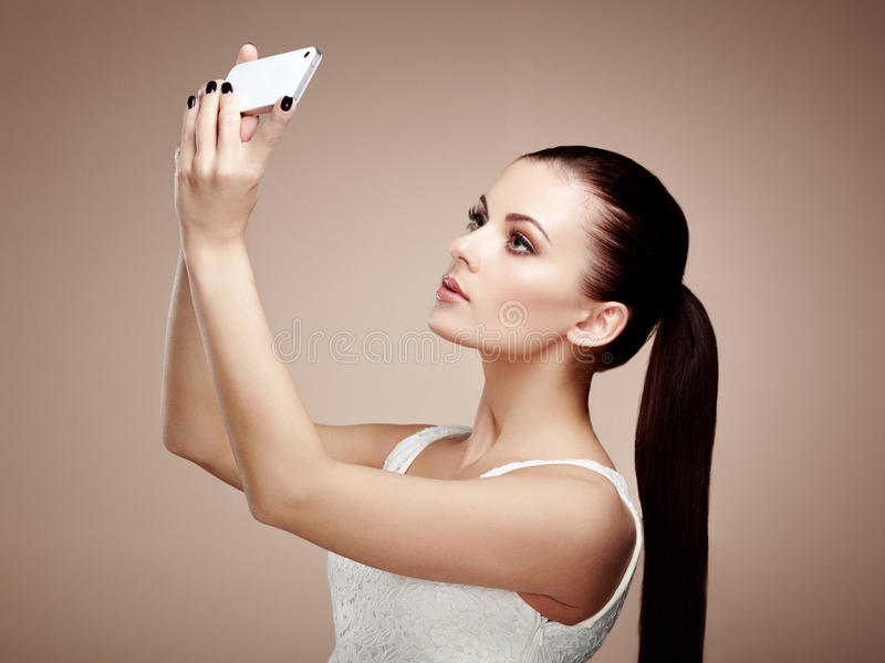 Beautiful young woman taking selfie. Girl photographing herself with phone. Beauty fashion. Eyelashes. Cosmetic Eyeshadow royalty free stock photography