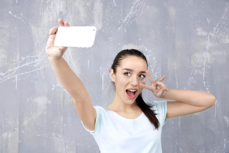 Beautiful young woman taking selfie. Near grunge wall royalty free stock photography