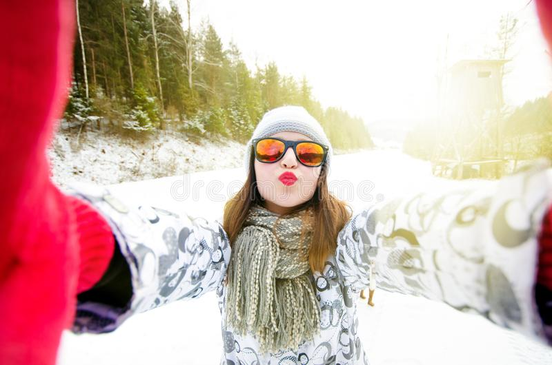 Beautiful young woman taking a selfie in winter nature. Pretty woman taking a photo in a nature. Winter background. royalty free stock images