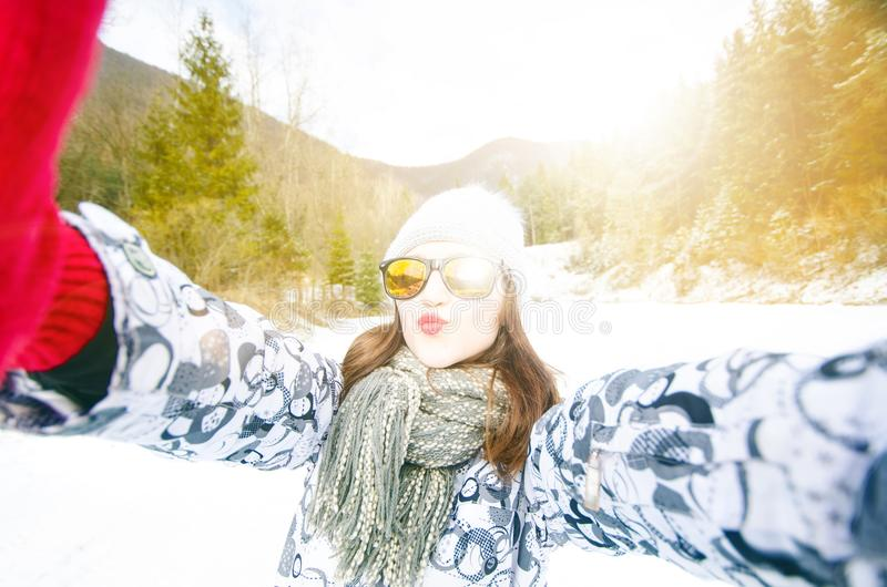 Beautiful young woman taking a selfie in winter nature. Pretty woman taking a photo in a nature. Winter background. stock photography