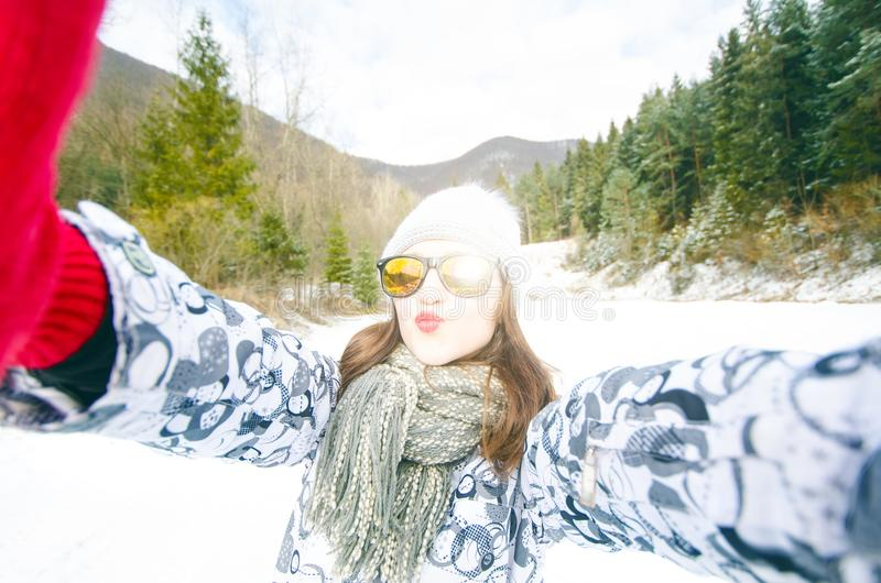 Beautiful young woman taking a selfie in winter nature. Pretty woman taking a photo in a nature. Winter background. royalty free stock photography