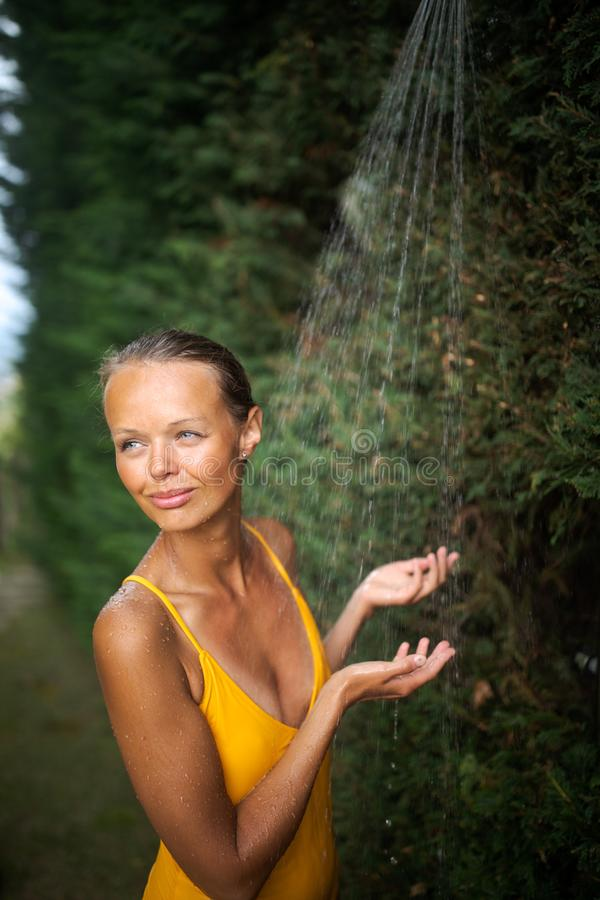 Beautiful young woman taking a shower outdoors royalty free stock images