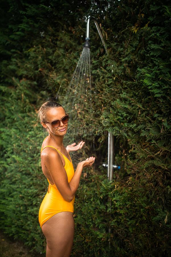 Beautiful young woman taking a shower outdoors royalty free stock image