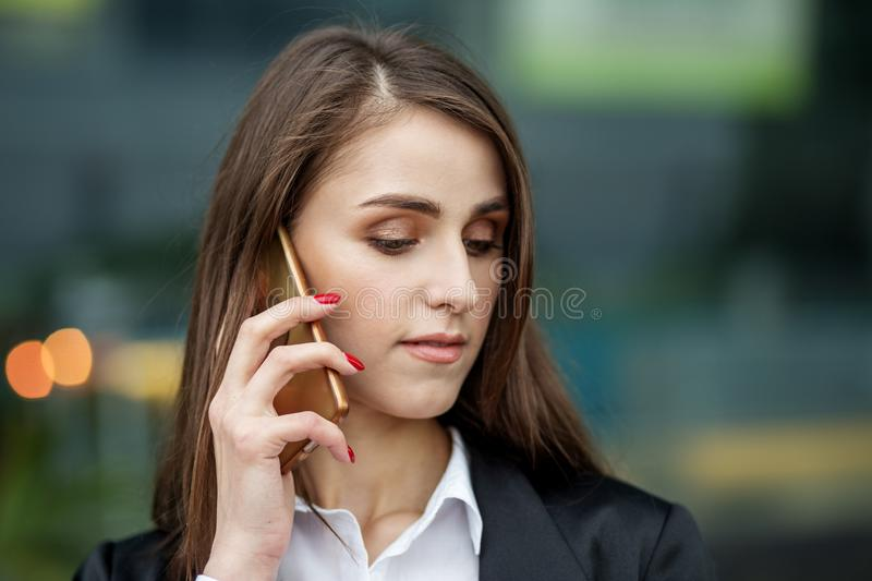 Beautiful young woman talking on a mobile phone. The concept of the Internet, technology, business, communication and lifestyle stock photography