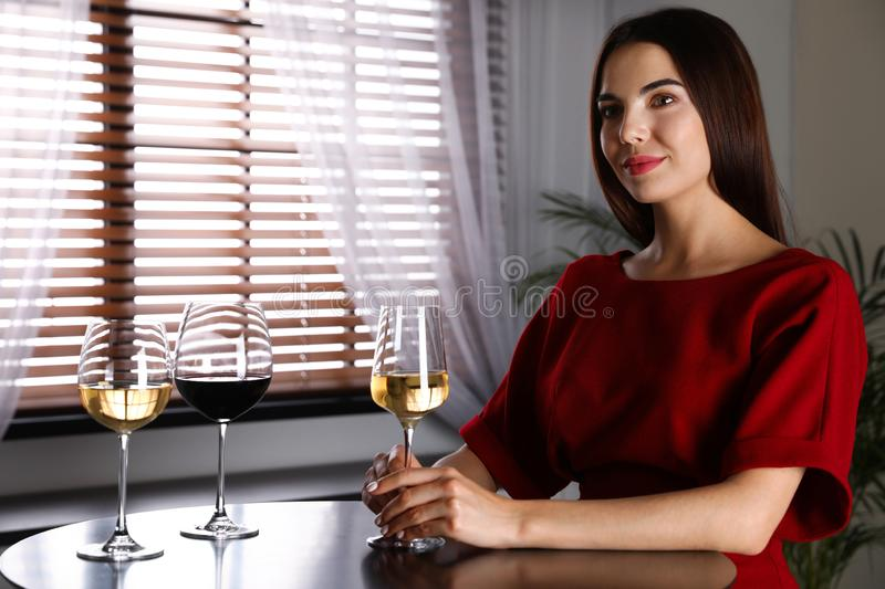 Beautiful young woman tasting luxury wine at table. Space for text stock photography