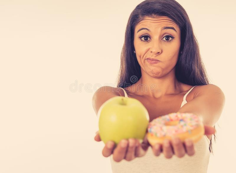 Attractive young woman on a diet deciding between an apple and a doughnut stock photos