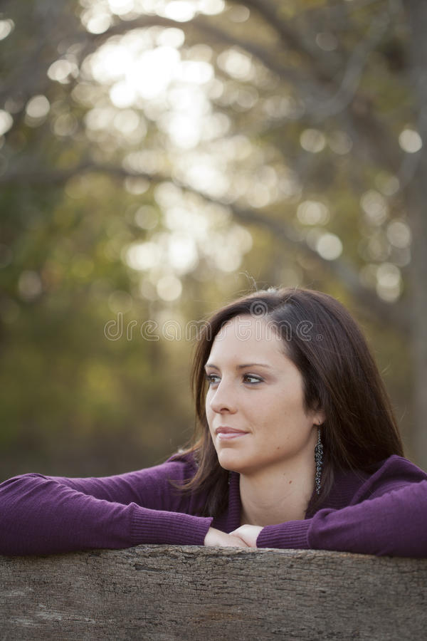 Beautiful Young Woman Thinking Outside. Pretty young woman thinking and looking off in the distance stock photography
