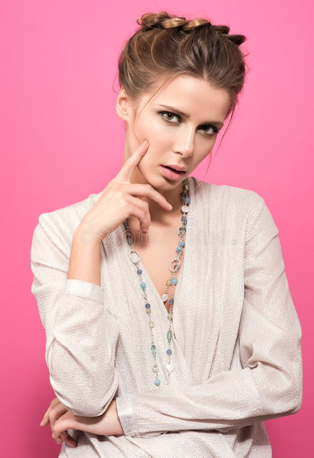 Beautiful young woman thinking on something, touching fingers to face. Stylish appearance, hair style and light makeup. Bright blouse and a chain with beads at royalty free stock images