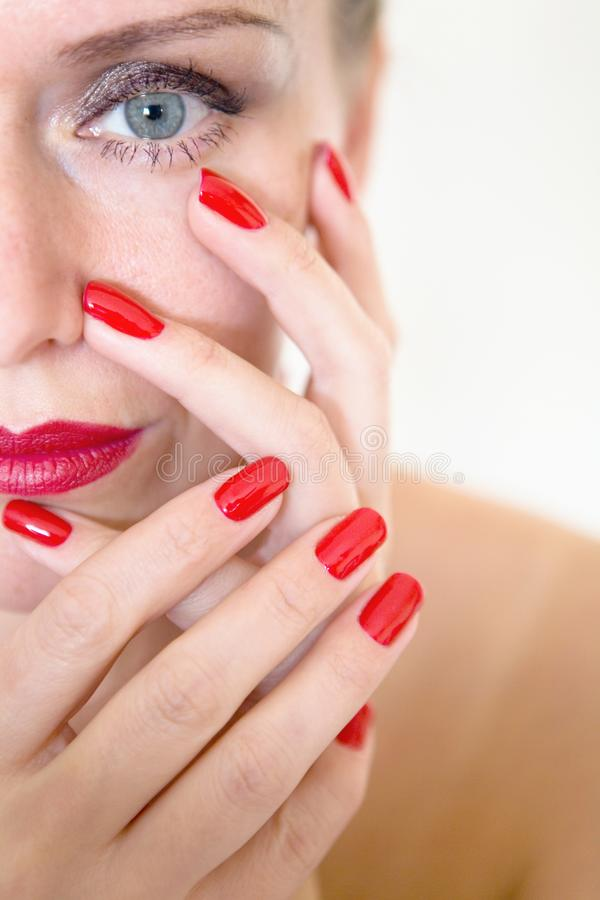 A beautiful young woman is touching her face with her fingers. Makeup and manicure stock images