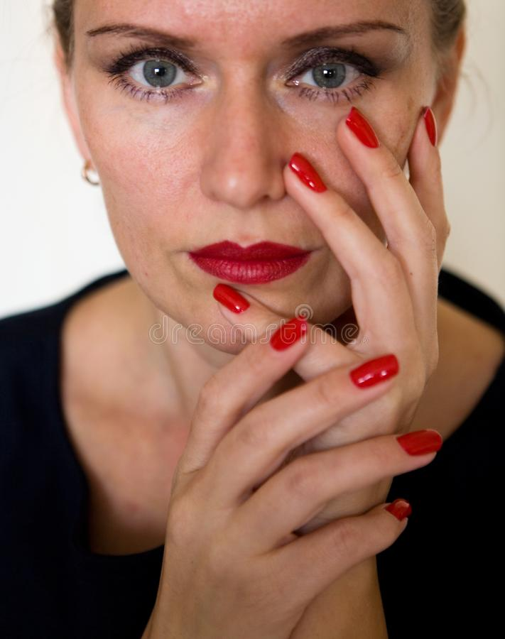 A beautiful young woman is touching her face with her fingers. Makeup and manicure stock image