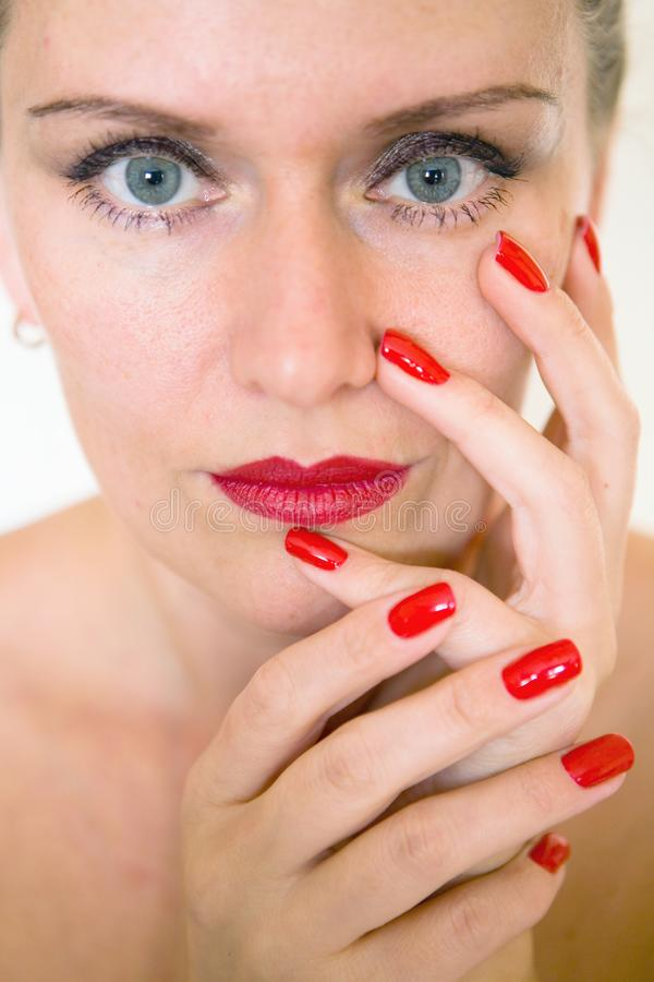 A beautiful young woman is touching her face with her fingers. Makeup and manicure royalty free stock photos