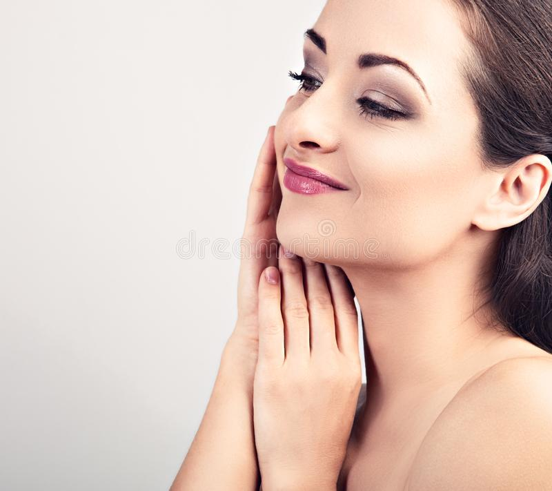 Beautiful young woman touching herself face skin. Smiling female model applying skincare moisturizer on the face. Beauty and anti stock image