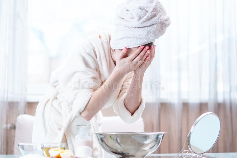 Beautiful young woman with a towel on head washing face with water in the morning. Hygiene and care for the skin stock image