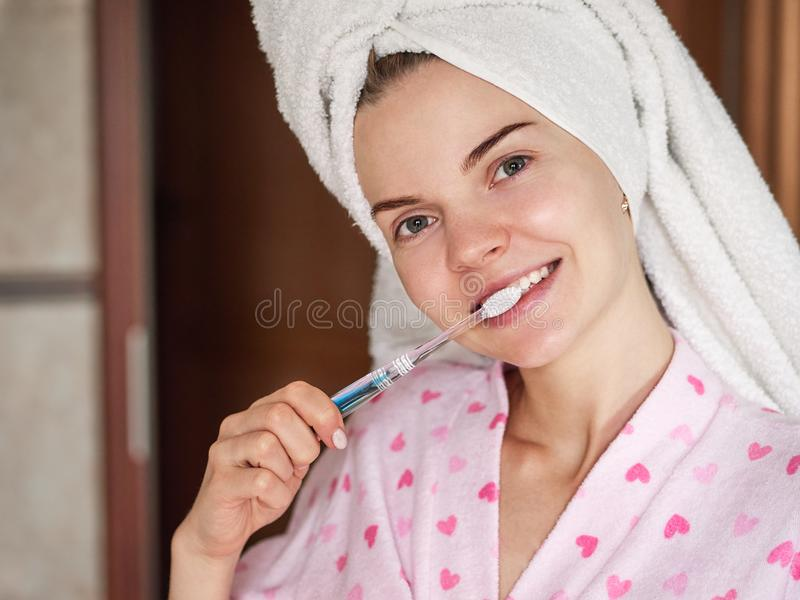 Beautiful young woman in towel turban after morning shower posing in bathroom in front of window with toothbrush and adorable stock photo