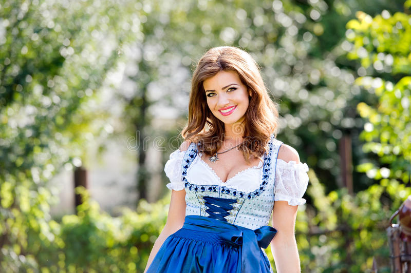 Beautiful young woman in traditional bavarian dress in park. Beautiful young woman in traditional bavarian dress standing in the garden. Oktoberfest royalty free stock image