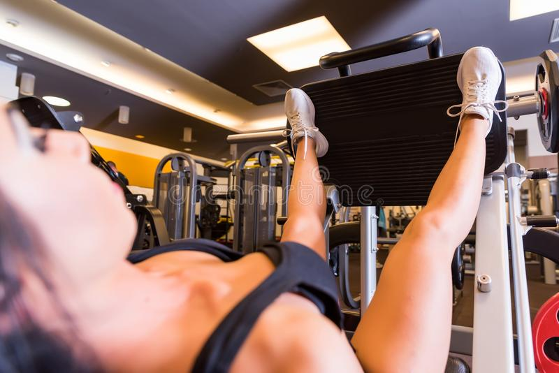 A young woman training her legs on a weight lifting machine. A beautiful young woman training her legs on a weight lifting machine in the Gym.r royalty free stock images