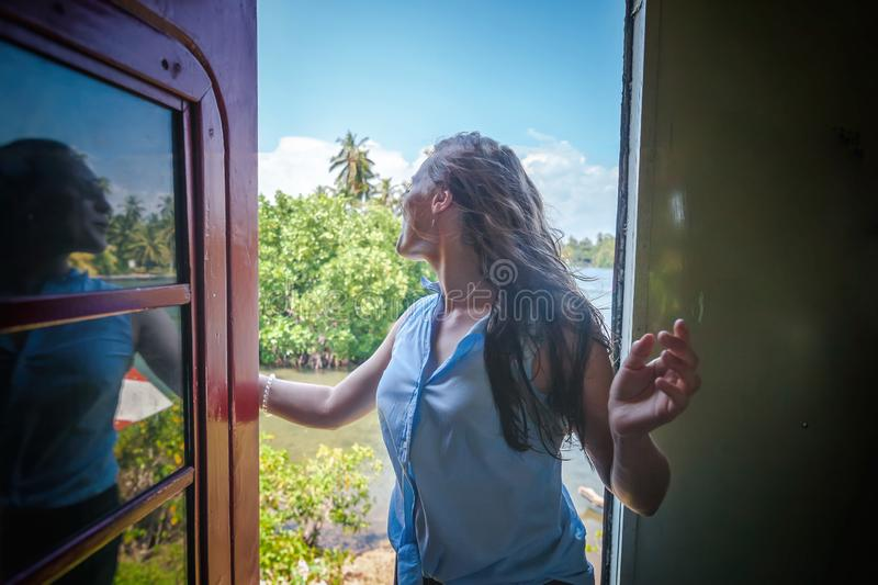 Beautiful young woman in a traveler hat in a carriage on a train in Sri Lanka traveling to Asia,. Island of Ceylon stock photography