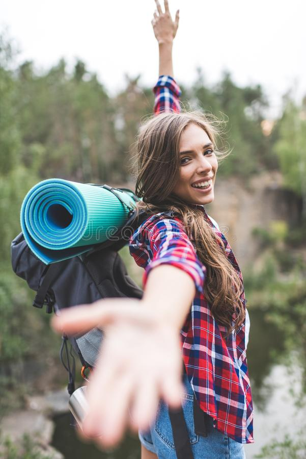 beautiful young woman with trekking backpack stretching hand out to royalty free stock photography