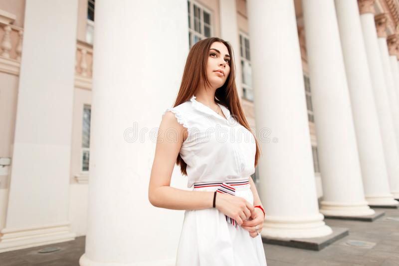 Beautiful young woman in a trendy white dress stock photo