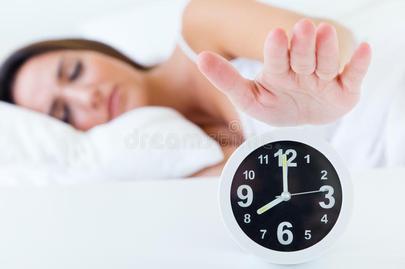 Beautiful young woman turning off the alarm clock imagenes de archivo