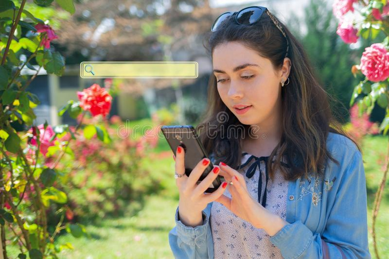 Beautiful young woman typing on phone. Roses on the background. Blank for Copy space. Sign of searching. Concept of modern royalty free stock photography