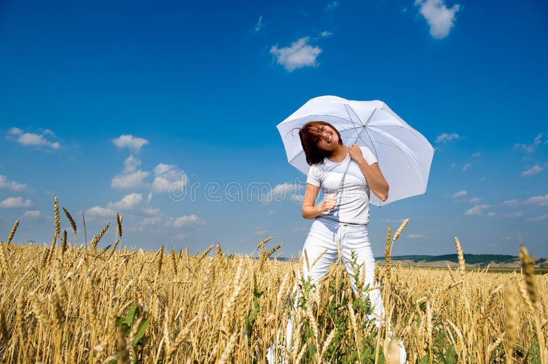 Beautiful young woman under blue sky. With umbrella in the field. Smiling face royalty free stock photo