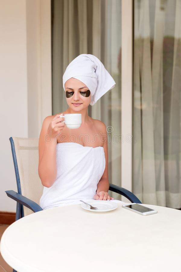 Beautiful young woman with under eye patches in bathrobe holding cup of coffee and drink drinking . Happy girl relax in hotel stock images