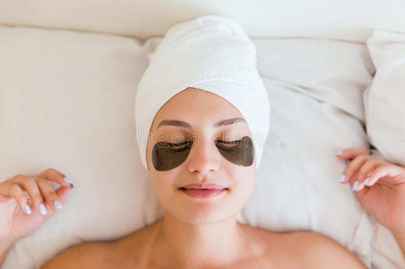 Beautiful young woman with under eye patches in bathrobe lying in bed. Happy girl taking care of herself. Beauty skincare and stock image