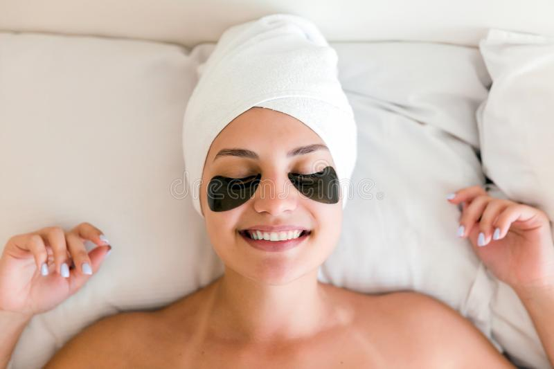 Beautiful young woman with under eye patches in bathrobe lying in bed. Happy girl taking care of herself. Beauty skincare and. Wellness morning concept royalty free stock photo
