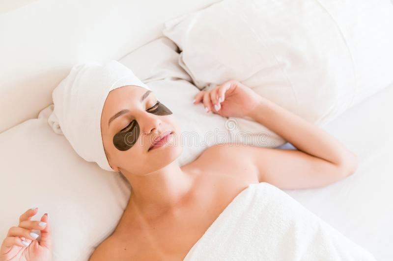 Beautiful young woman with under eye patches in bathrobe lying in bed. Happy girl taking care of herself. Beauty skincare and. Wellness morning concept stock images