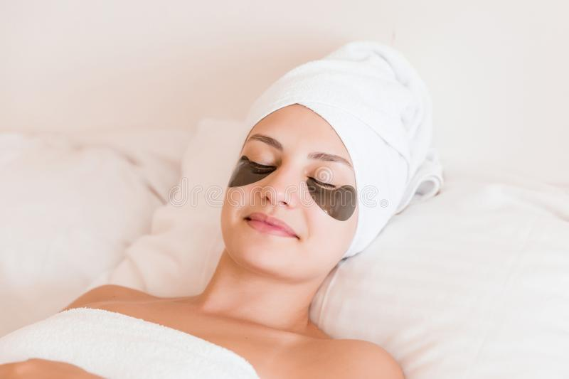 Beautiful young woman with under eye patches in bathrobe lying in bed. Happy girl taking care of herself. Beauty skincare and. Wellness morning concept royalty free stock photography