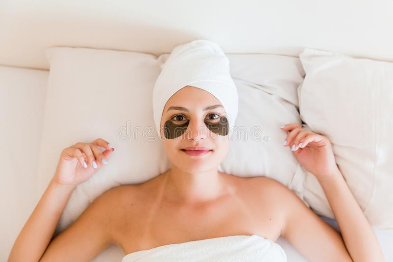 Beautiful young woman with under eye patches in bathrobe lying in bed. Happy girl taking care of herself. Beauty skincare and. Wellness morning concept stock photo
