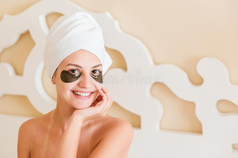 Beautiful young woman with under eye patches in bathrobe sitting in bed. Happy girl taking care of herself. Beauty skincare and. Wellness morning concept royalty free stock photos