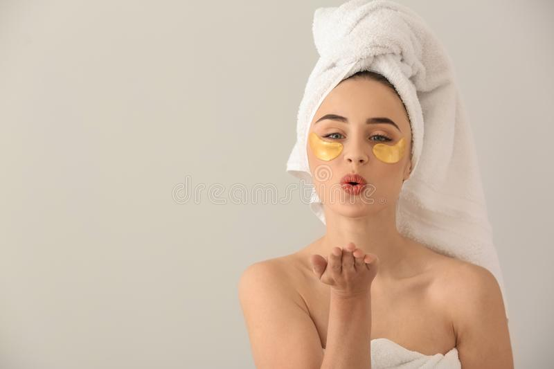 Beautiful young woman with under-eye patches blowing kiss on light background stock photos