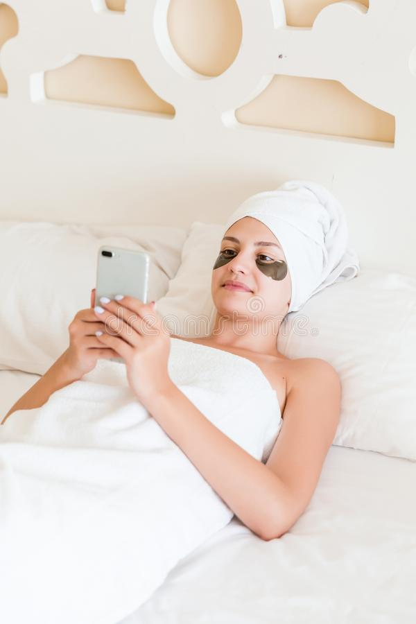 Beautiful young woman with under eye patches and using mobile phone in bathrobe lying in bed. Happy girl taking care of herself. royalty free stock images