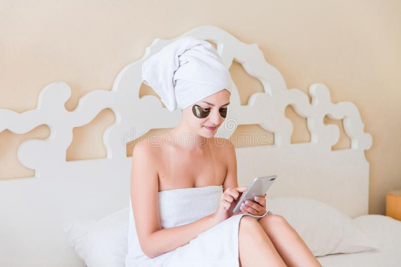 Beautiful young woman with under eye patches and using mobile phone or writing sms massage in bathrobe lying in bed. Happy girl royalty free stock photo