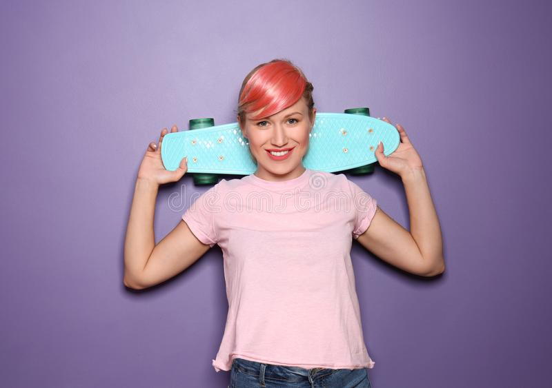 Beautiful young woman with unusual hair holding skateboard on color background stock photos