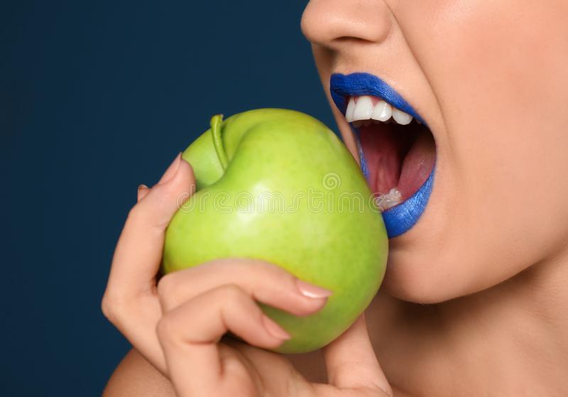 Beautiful young woman with unusual lipstick and apple on color background, closeup royalty free stock photos
