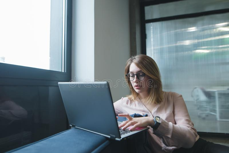 A beautiful young woman uses a laptop on the sofa in the office. Freelancer works in coworking stock photo