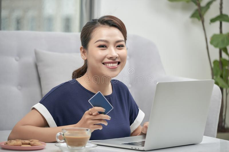 Beautiful young woman using credit card and laptop for online shopping stock photos
